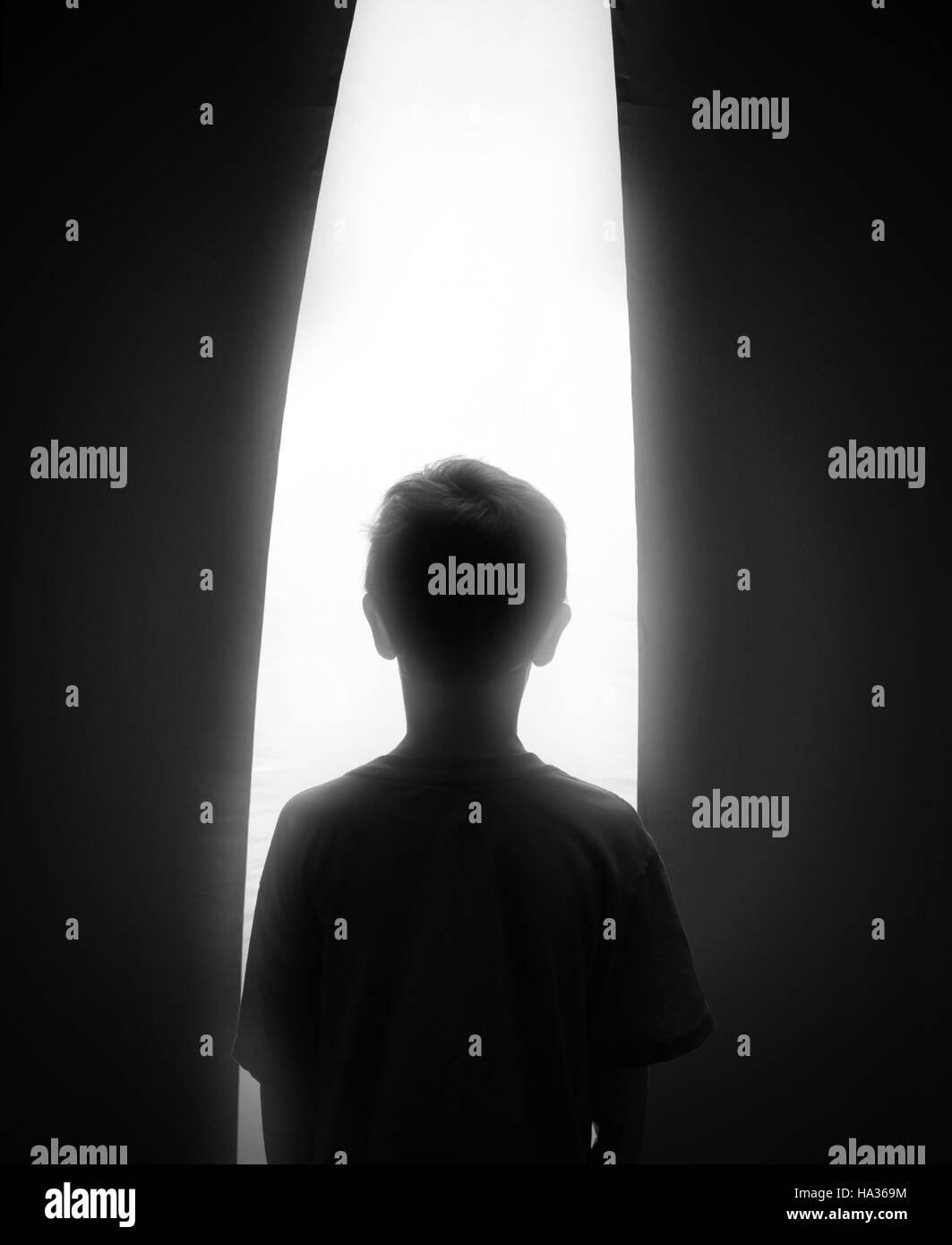 Eine schwarze und weiße Silhouette eines kleinen Jungen auf der Suche in einem hellen weißen Fenster für Stockbild