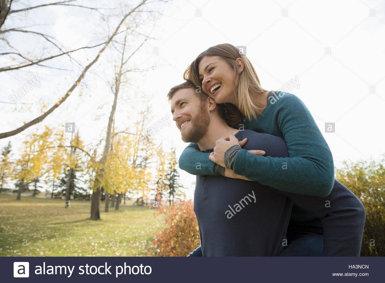 Glückliches Paar Huckepack im Herbst park Stockbild