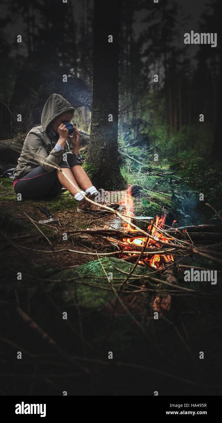 junge Frau trinken heißen Tee durch das Feuer im Wald Stockbild