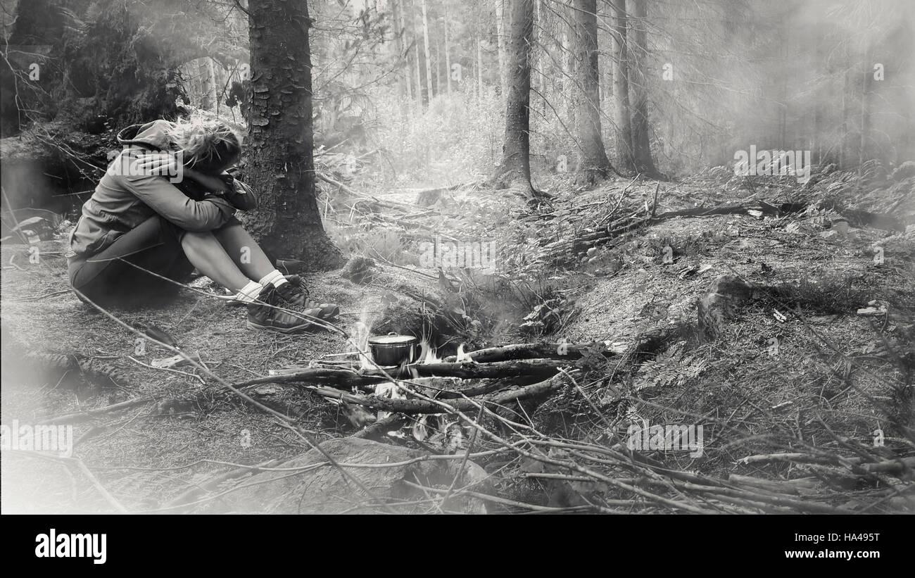 junge Frau im Wald allein am Feuer sitzen Stockbild