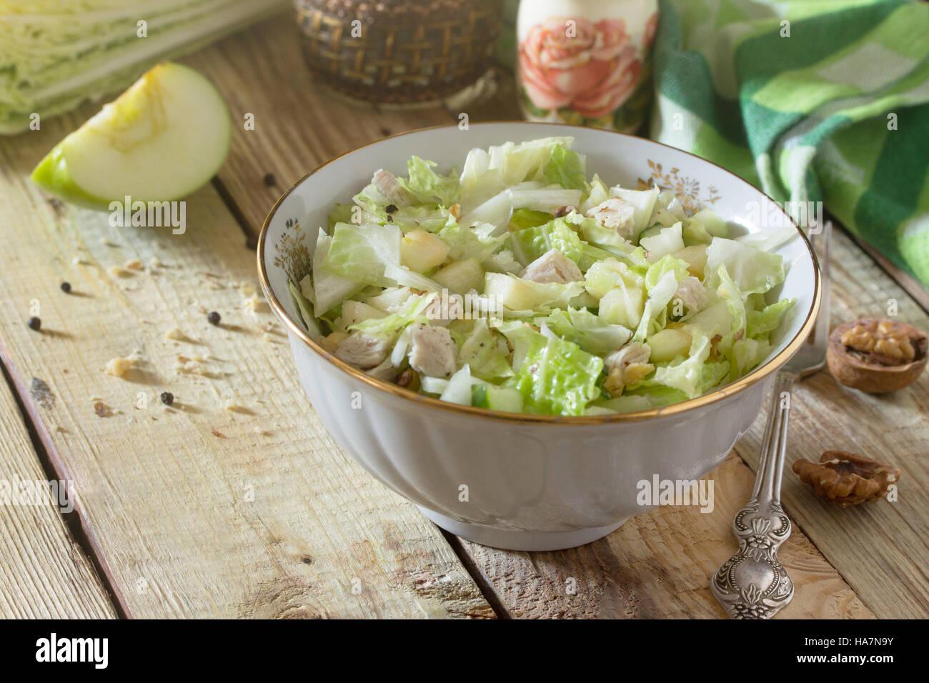 Salat mit Kohl, Huhn, Apfel, Gurke und Walnüsse. Gesunde Ernährung-Konzept. Ansicht von oben. Stockbild