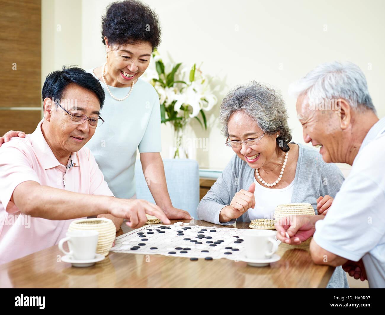 zwei hochrangige asiatische Männer spielen Weiqi (oder Go-Spiel) zu Hause mit ihren Frauen beobachten. Stockbild