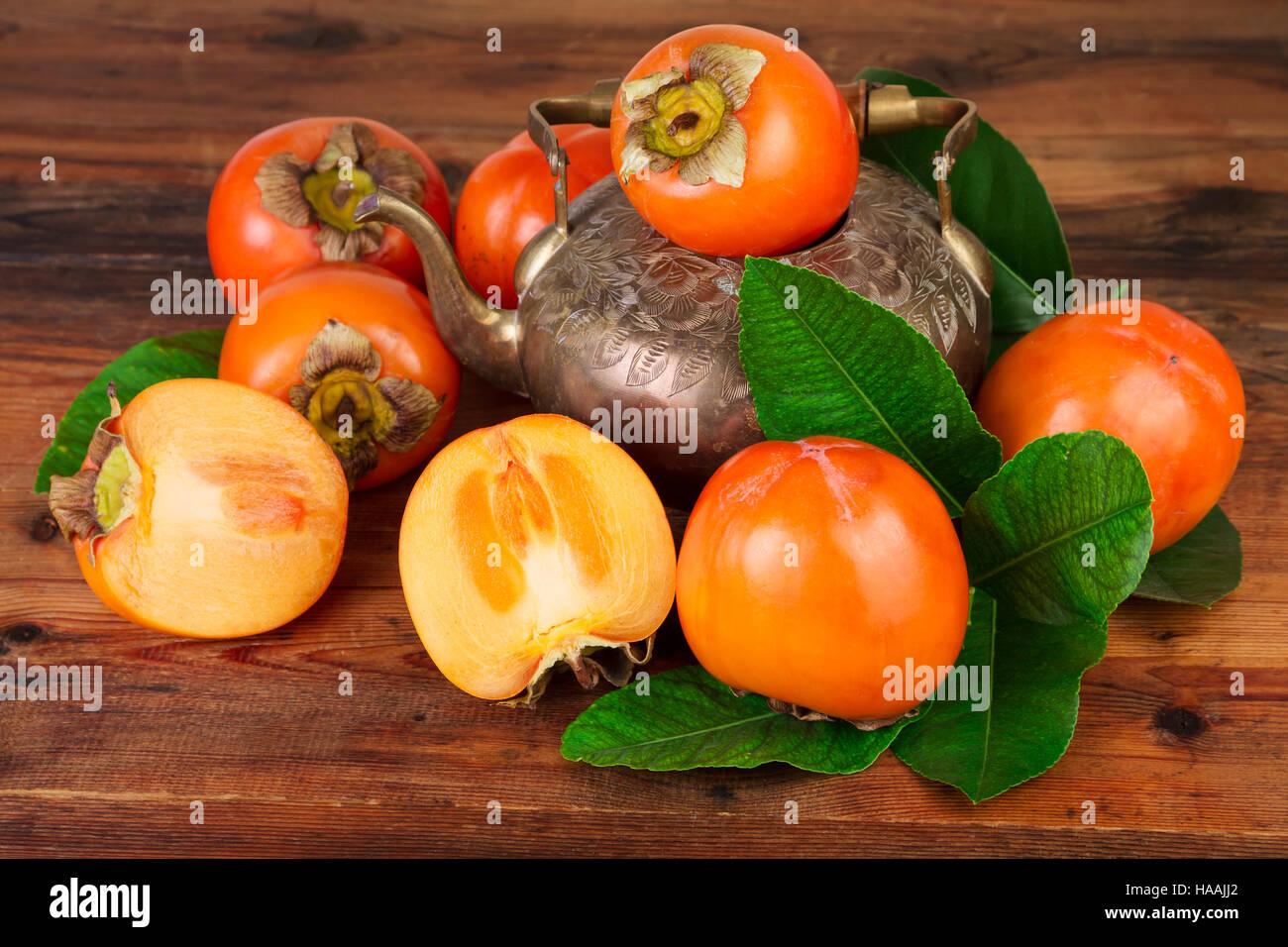 Reife Kaki Früchte mit Vintage Teekanne. Orientalische Osten persische Stillleben. Stockfoto