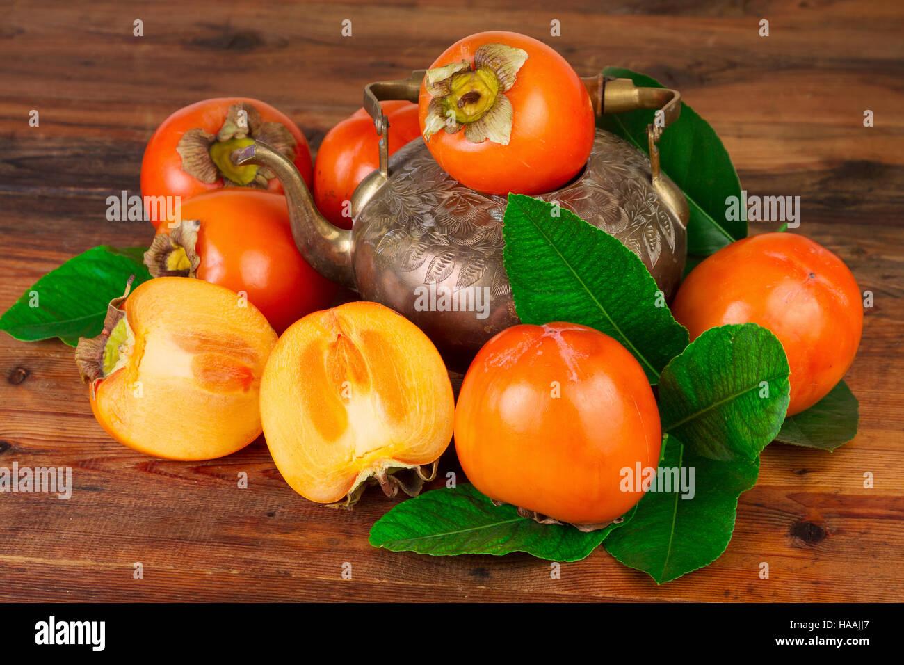 Kaki Kaki Frucht mit Vintage Teekanne. Orientalische Osten persische Stillleben. Stockfoto