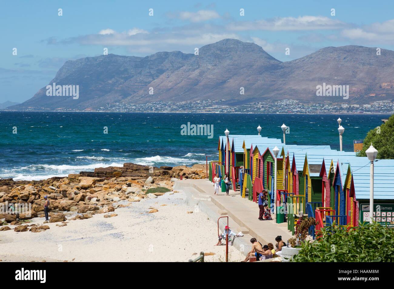 Farbenfrohe Strandhütten und Menschen am Strand von Muizenberg, Western Cape, Südafrika Stockfoto