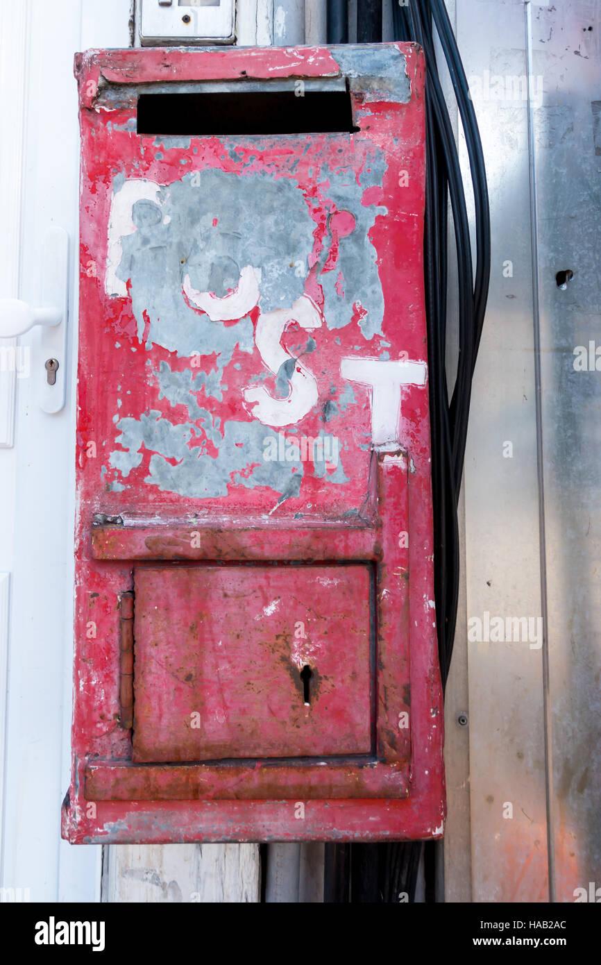 Metall Briefkasten lackiert rot mit abgeplatzte Farbe und bare-Metal durchscheint. Stockbild