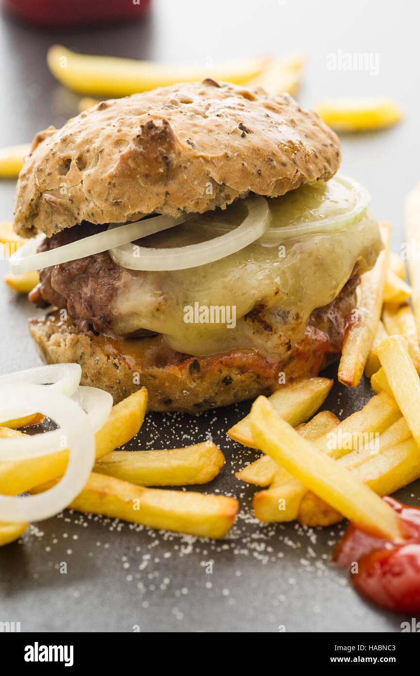 Hausgemachter Cheeseburger mit Pommes frites, Zwiebelscheiben Stockbild