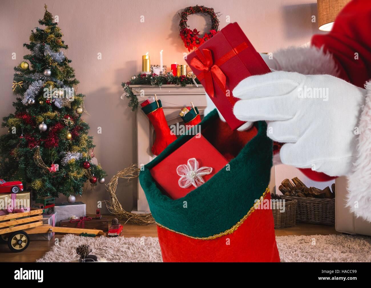 Santa, die Geschenke in Weihnachts-Strumpf im Wohnzimmer setzen ...