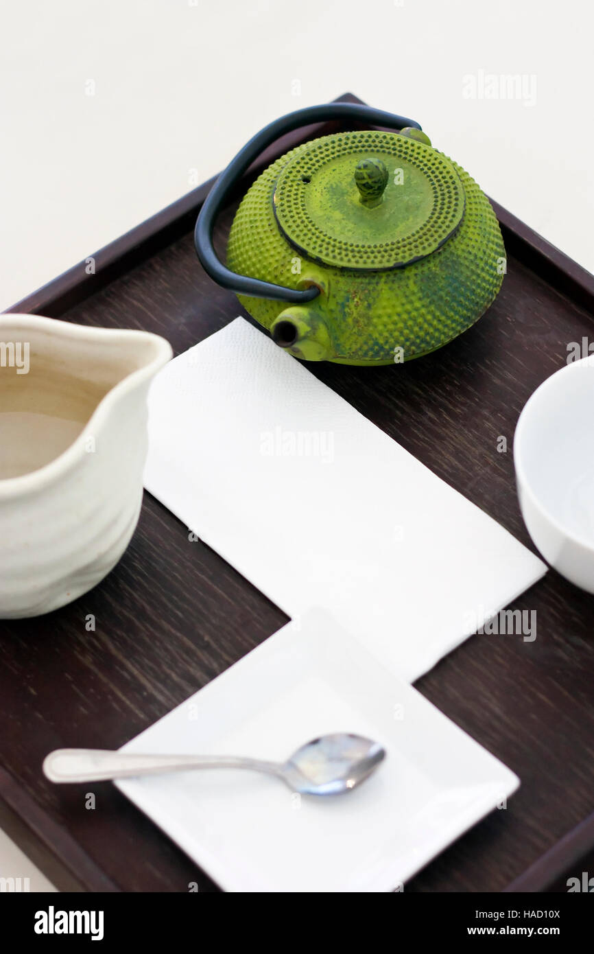 Tee-Set mit grünen Teekanne, weiß Teetasse, weiße Untertasse, Teelöffel auf Tablett aus Holz Stockbild