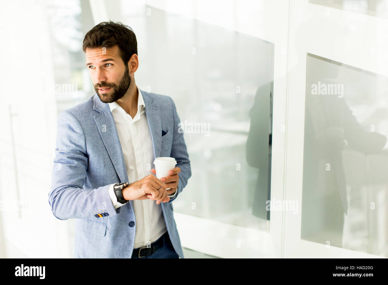 Geschäftsmann im Anzug, eine Tasse Kaffee in einem Bürogebäude und Blick auf die Uhr Stockfoto