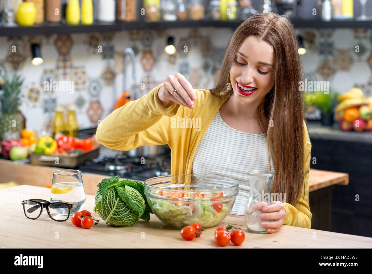Frau in der Küche mit Salat Stockbild