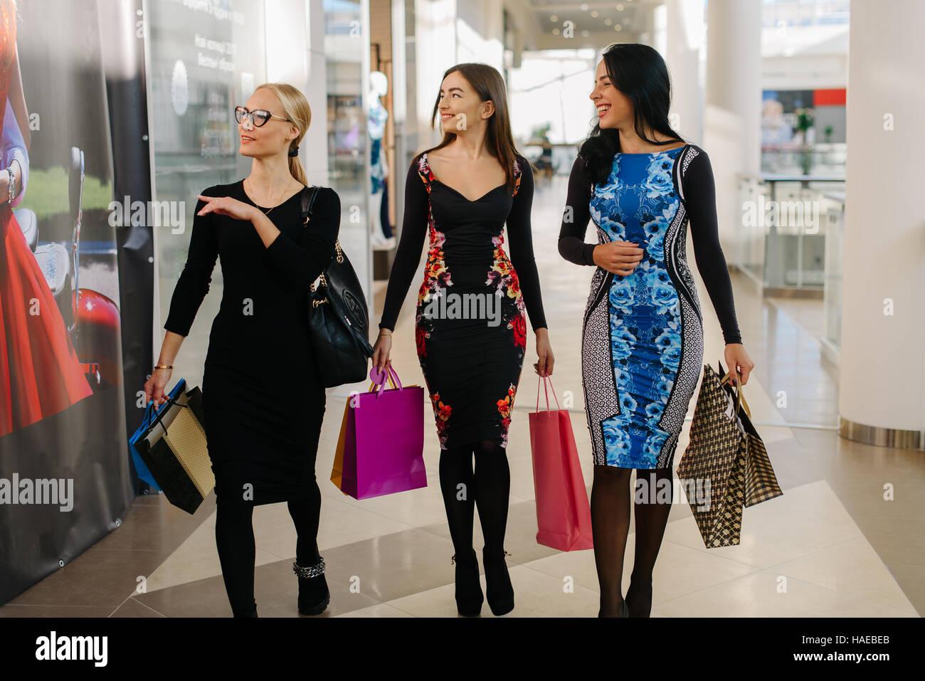6cb0a14c5d Drei attraktive Frauen haben in großen Einkaufszentrum einkaufen. Frauen  tragen Kleider und Einkaufstüten in der Hand haben.