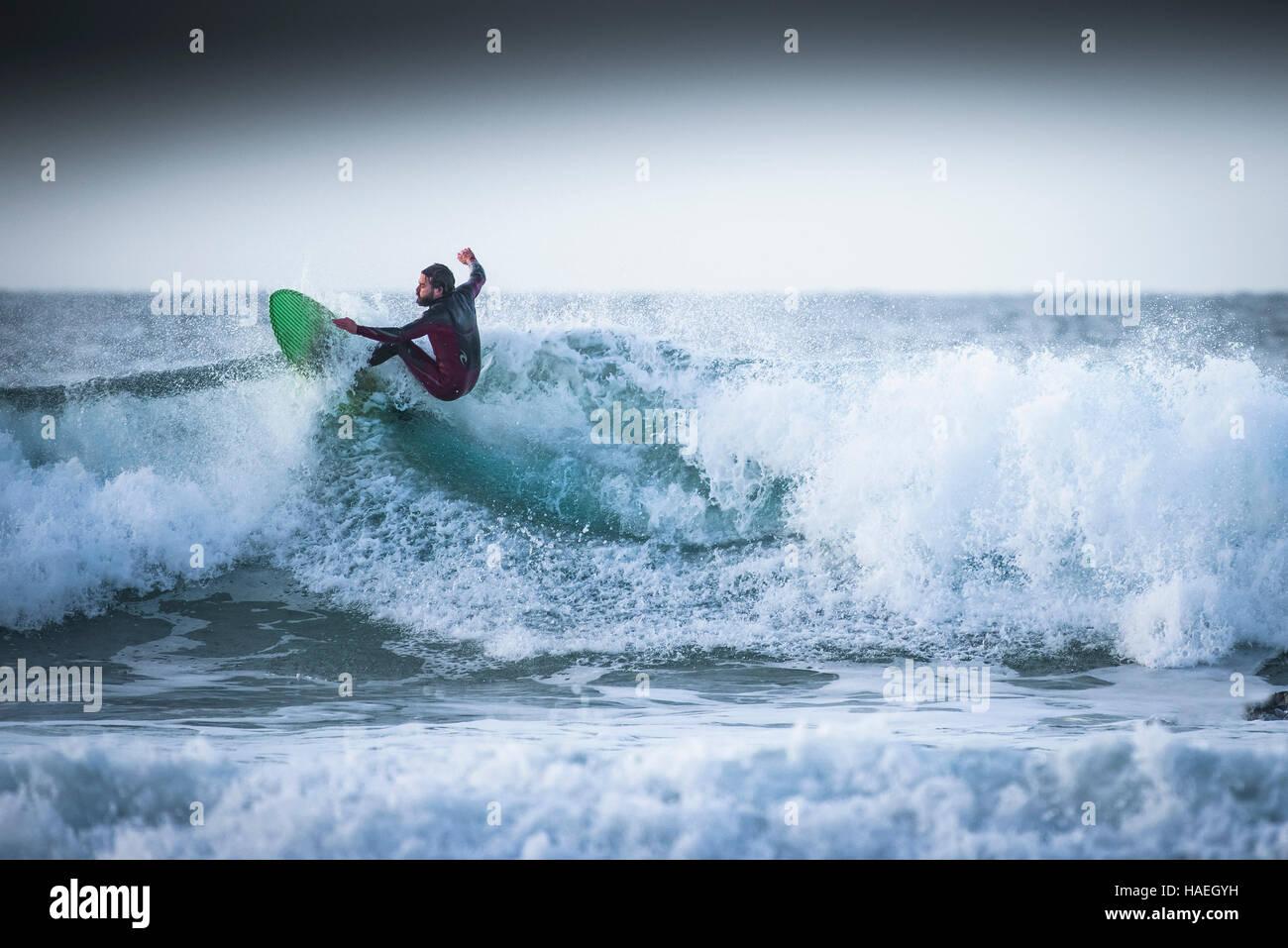 Ein Surfer reitet eine Welle an Fistral in Newquay, Cornwall. UK. Stockbild
