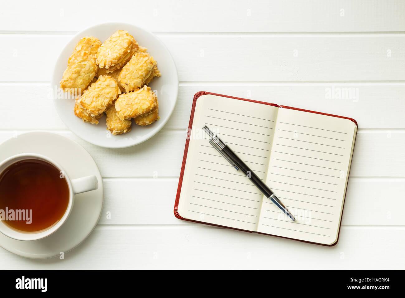 Leeren Notizblock mit Stift und Cookies mit Tee. Ansicht von oben. Stockbild