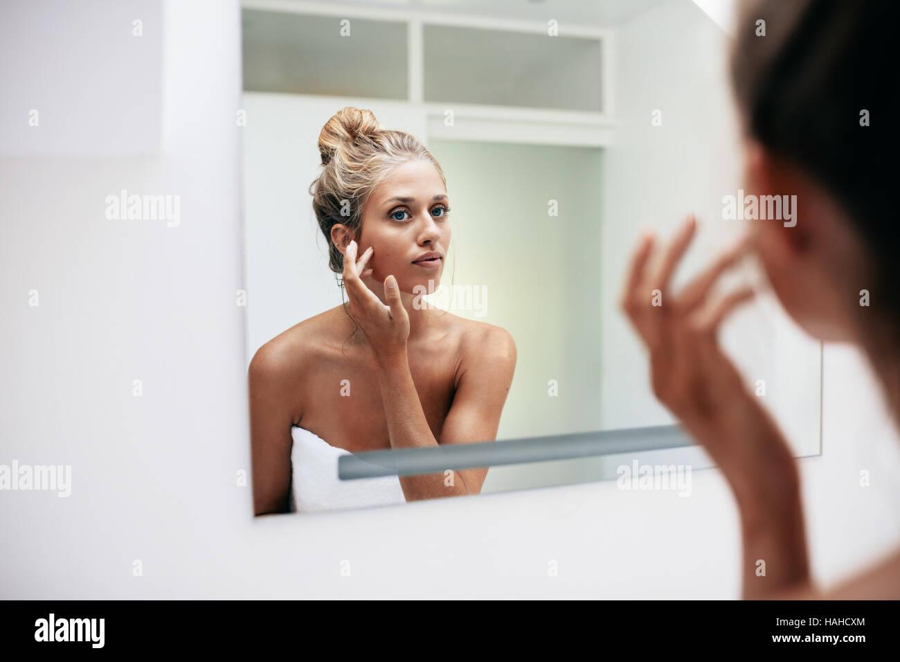 Schöne junge Frau steht im Badezimmer. Weibliche Blick in den Spiegel und berühren ihre Gesichtshaut. Stockfoto