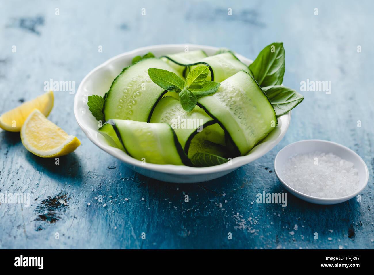 Schüssel mit frischen Gurken und Minze-Salat mit Meersalz und Zitrone Stockbild