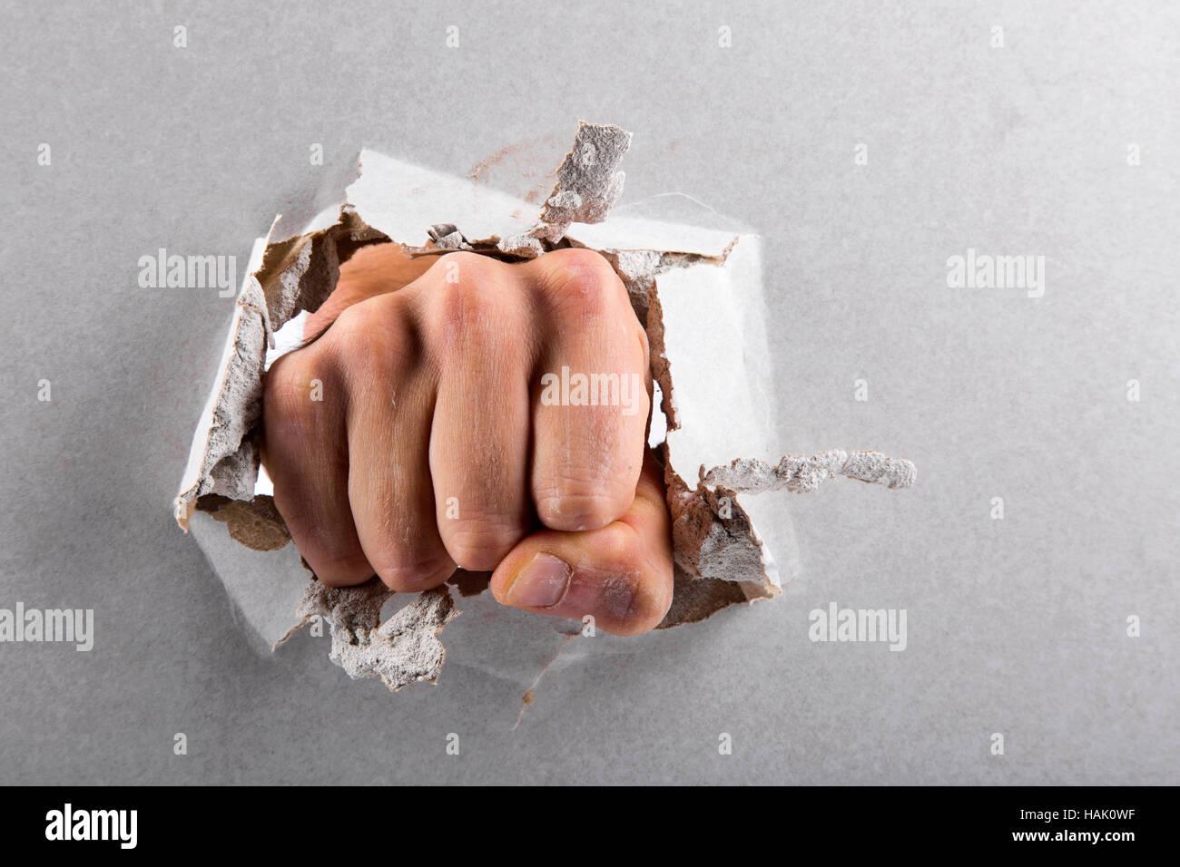 Aggression-Konzept, Wand durchbrochen von einer Faust Stockbild