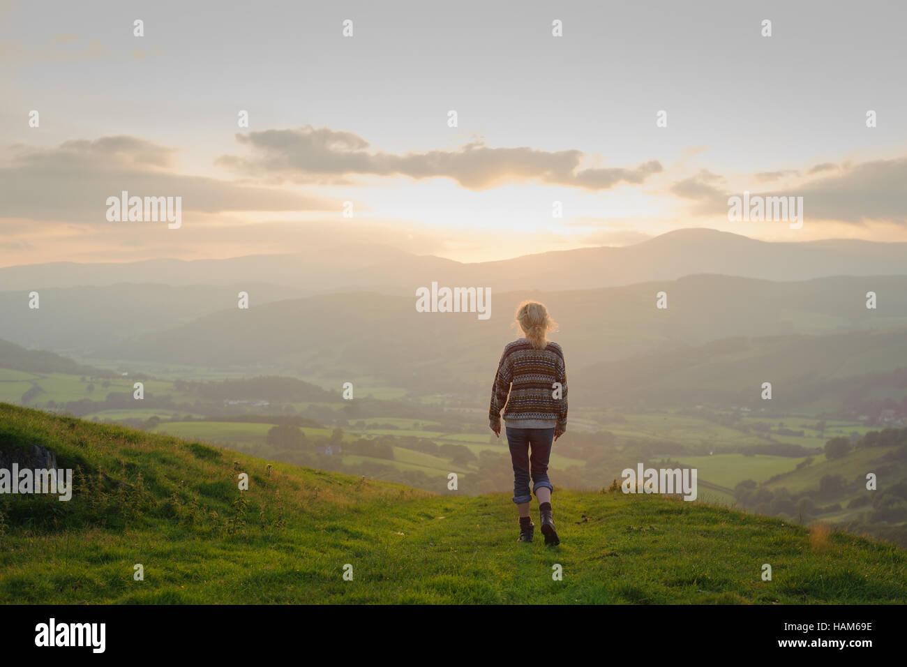Eine Frau, die zu Fuß in Richtung eines Tals in der Landschaft Stockbild