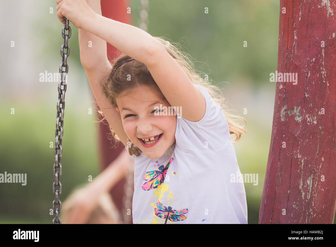 Junge Mädchen spielen mit Eisenkette auf Spielplatz Stockbild