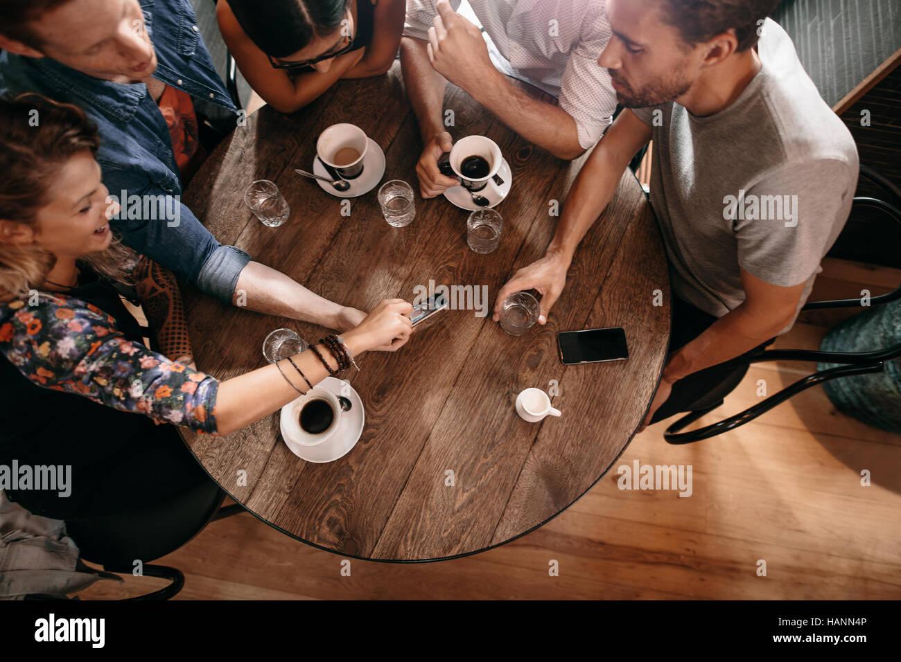 Draufsicht der Jugendlichen an einem Cafétisch sitzen und mit Blick auf Handy. Junge Männer und Frauen Stockbild