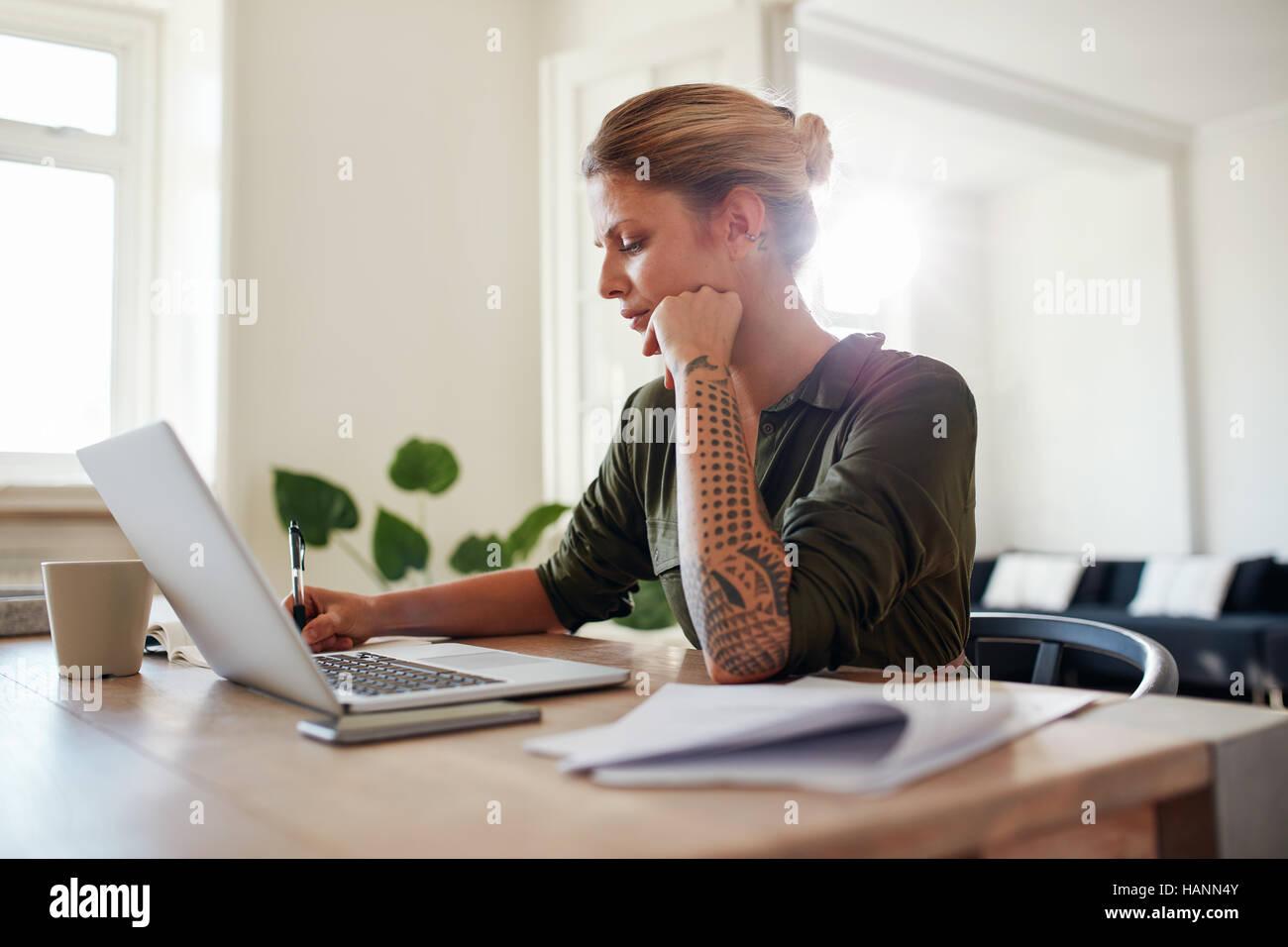 schuss von junge frau b ro zu hause arbeiten sch ne frau mit laptop und dokumente am tisch. Black Bedroom Furniture Sets. Home Design Ideas