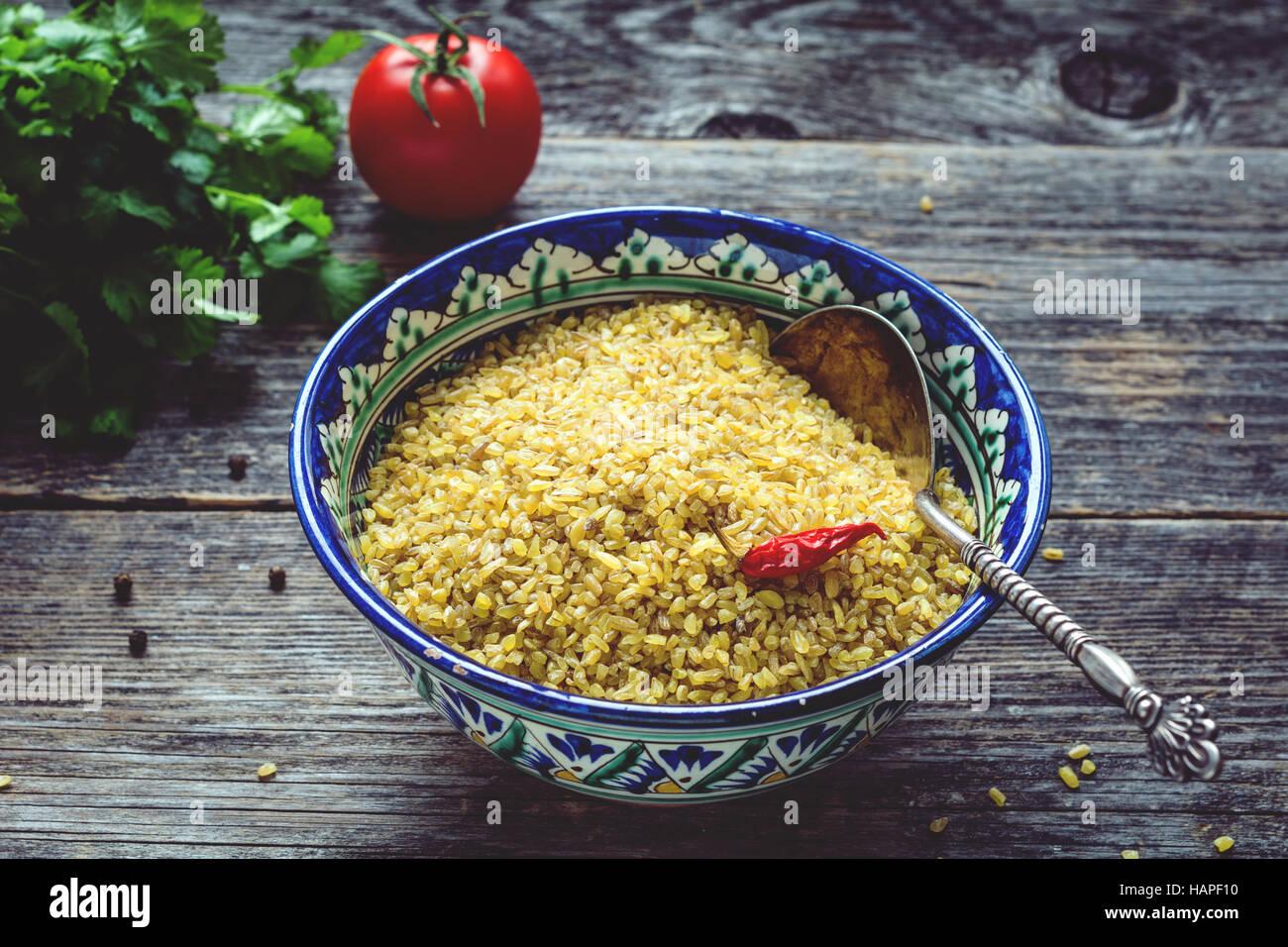 Rohe Bulgur Weizenkörner in bunten arabischen Schale, frische Petersilie, Tomaten und Paprika zum Kochen. Holztisch Stockfoto