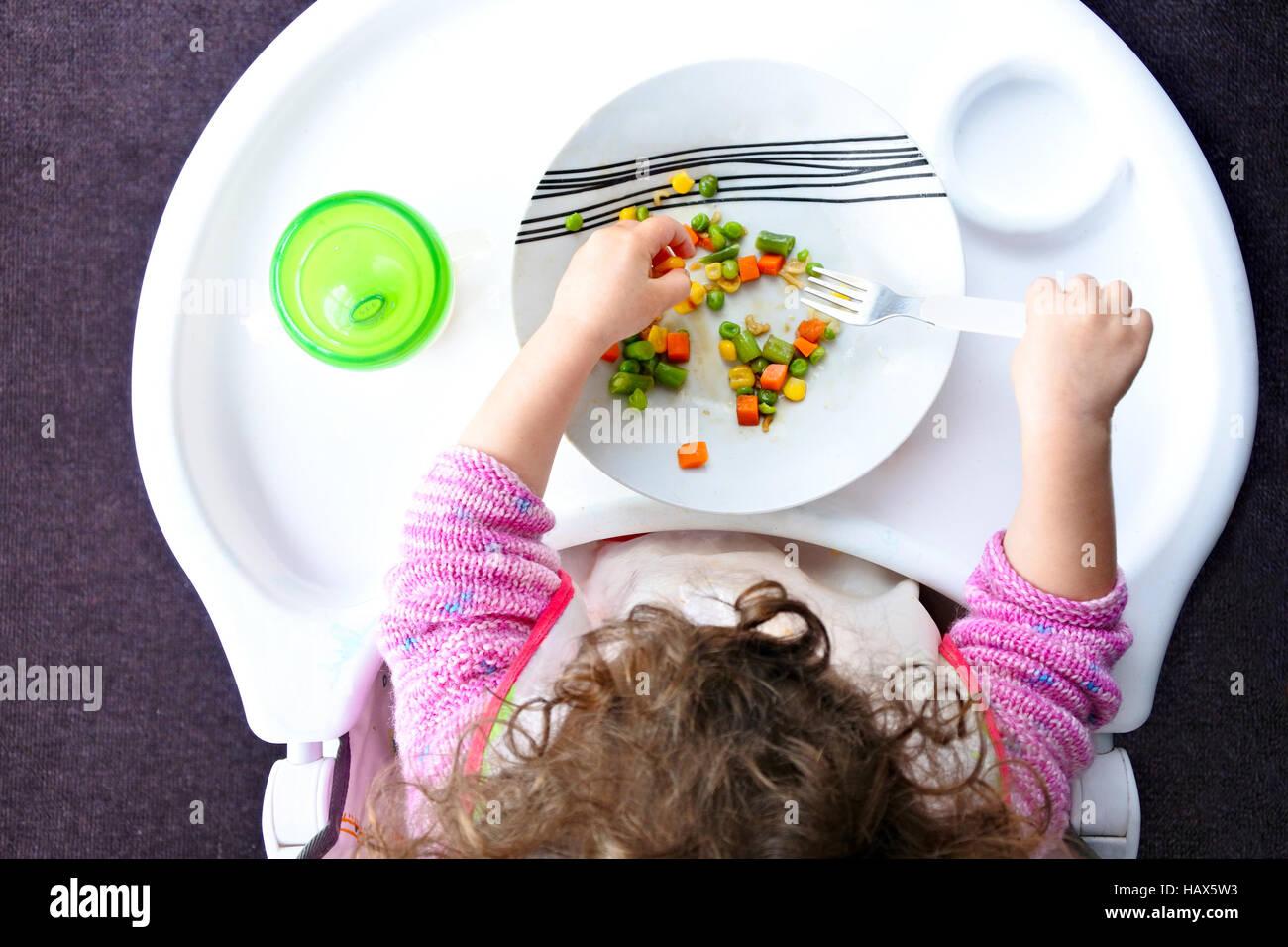 Über Blick auf ein kleines Kind isst Kind Gemüse. Kindheit und Kinder Gesundheits-Konzept. Echte Menschen. Stockbild