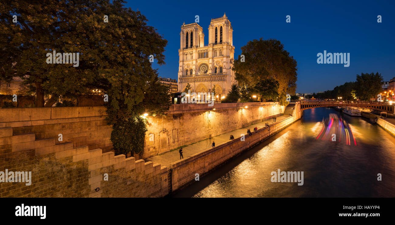 Kathedrale Notre Dame de Paris beleuchtet in der Dämmerung mit dem Seineufer und dem Pont au Double. Ile De Stockbild