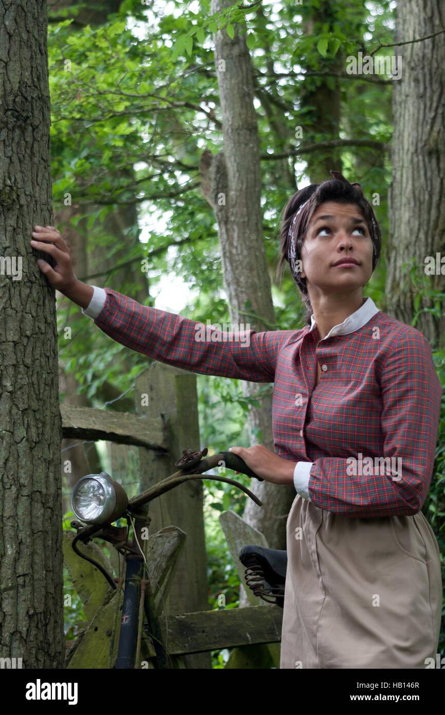 multikulturelle junge Frau im Vintage-Kleid mit rostigen alten Fahrrad Stockbild