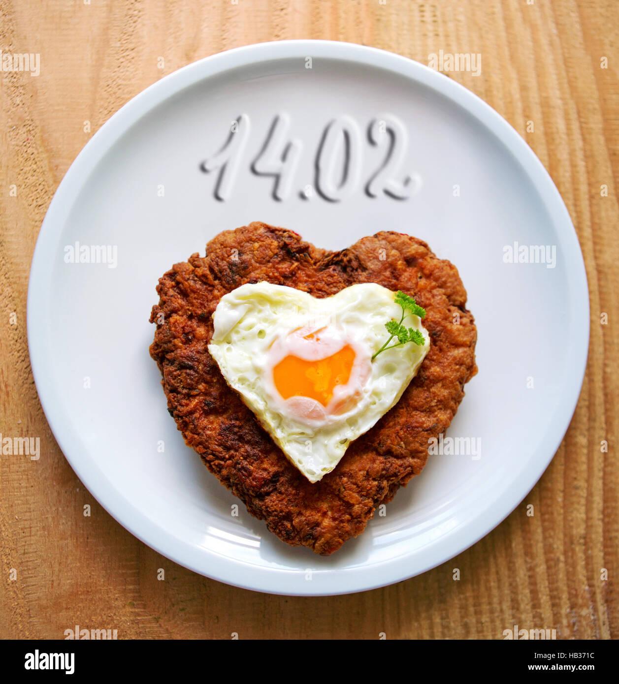 Herzförmige Hackfleisch Steak mit Spiegelei. Stockfoto