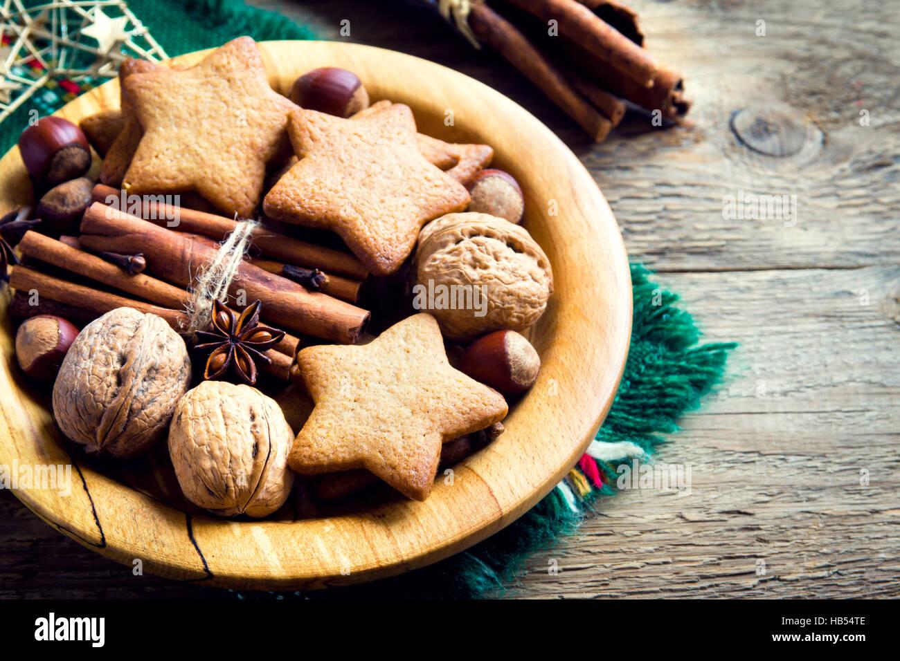 Rustikale Weihnachts-Dekoration mit Lebkuchen, Nüssen und weihnachtlichen Gewürzen auf Holzplatte hautnah Stockbild