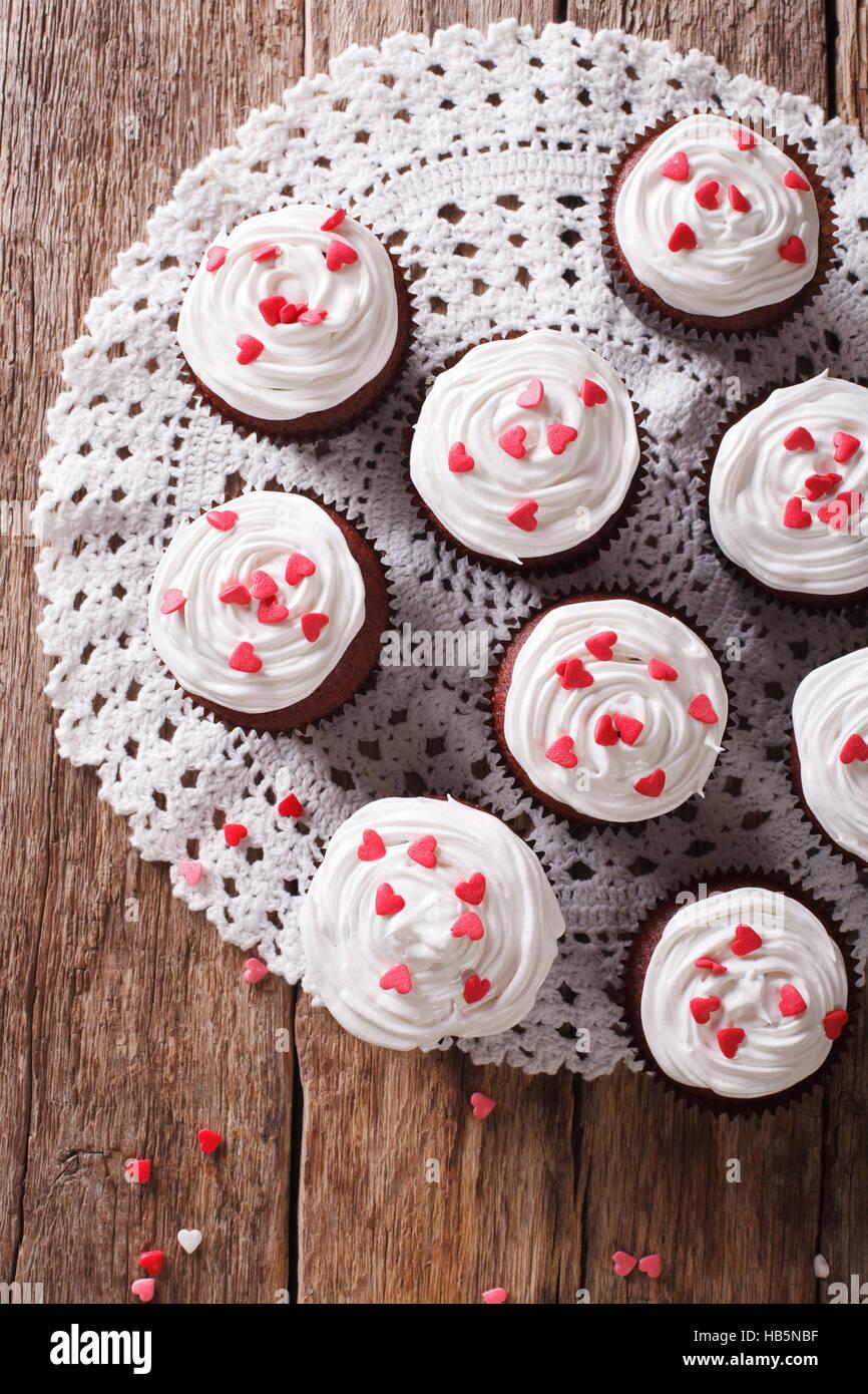 Red Velvet Cupcakes dekoriert mit Herzen Nahaufnahme auf dem Tisch. vertikale Ansicht von oben Stockfoto