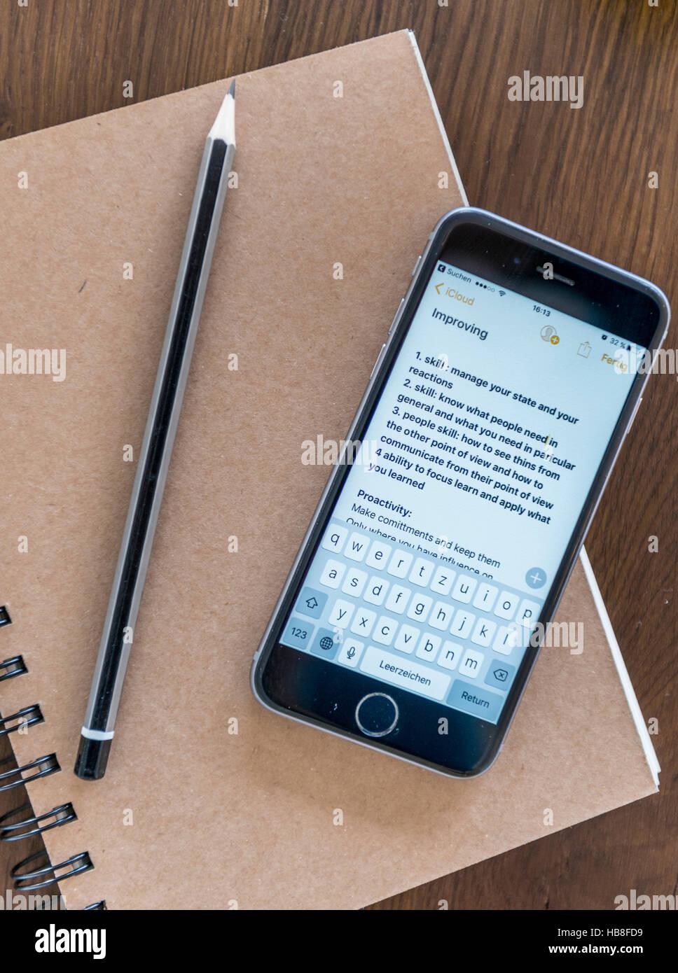 Hinweise zum Smartphone, Notizbuch und Stift auf einem Holztisch Stockbild