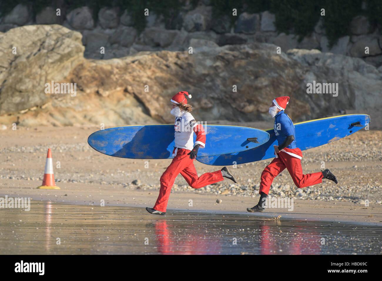 Surfen Sie Santas Rennen am Strand entlang in die jährliche Spendenaktion Santa Surf-Wettbewerb, an einem sehr Stockbild