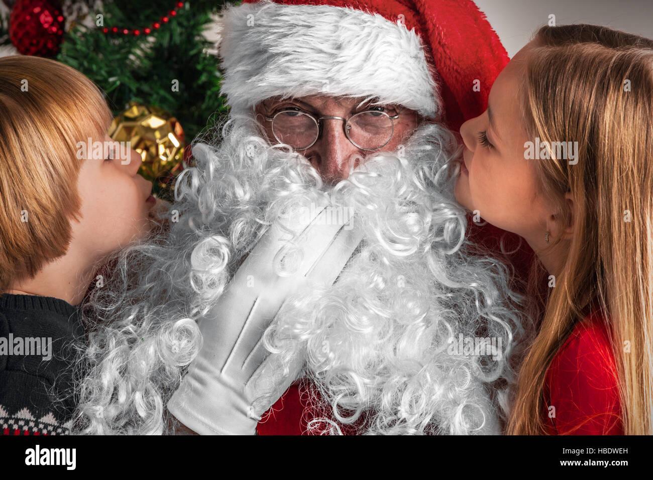 Kleine Kinder sagen Weihnachtswünsche in Santa Claus Ohr Stockfoto ...