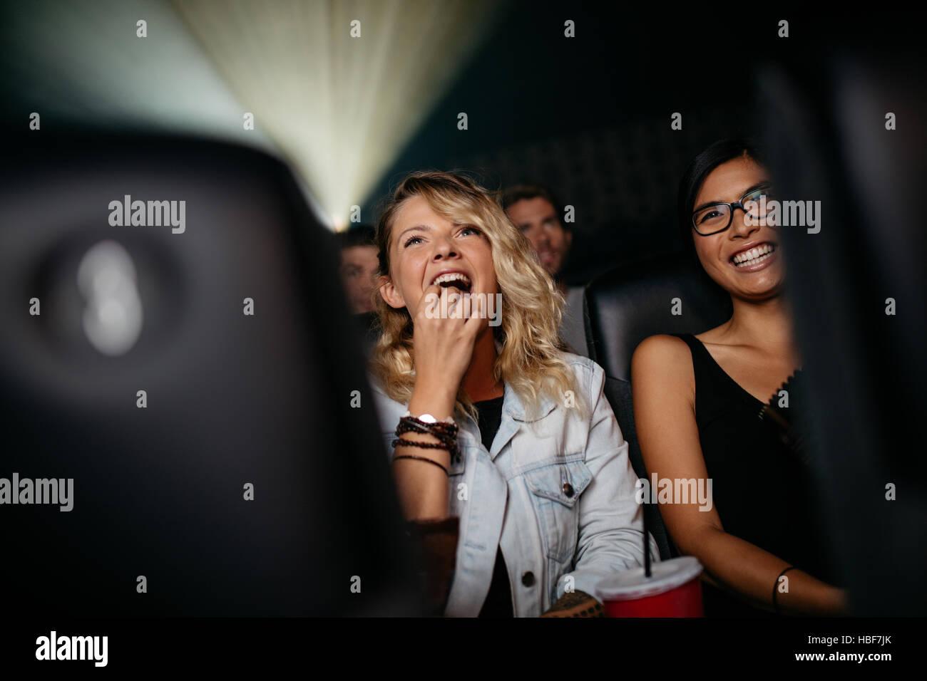 Lächelnde junge Frauen im Kinosaal Essen Popcorn und Film Stockbild