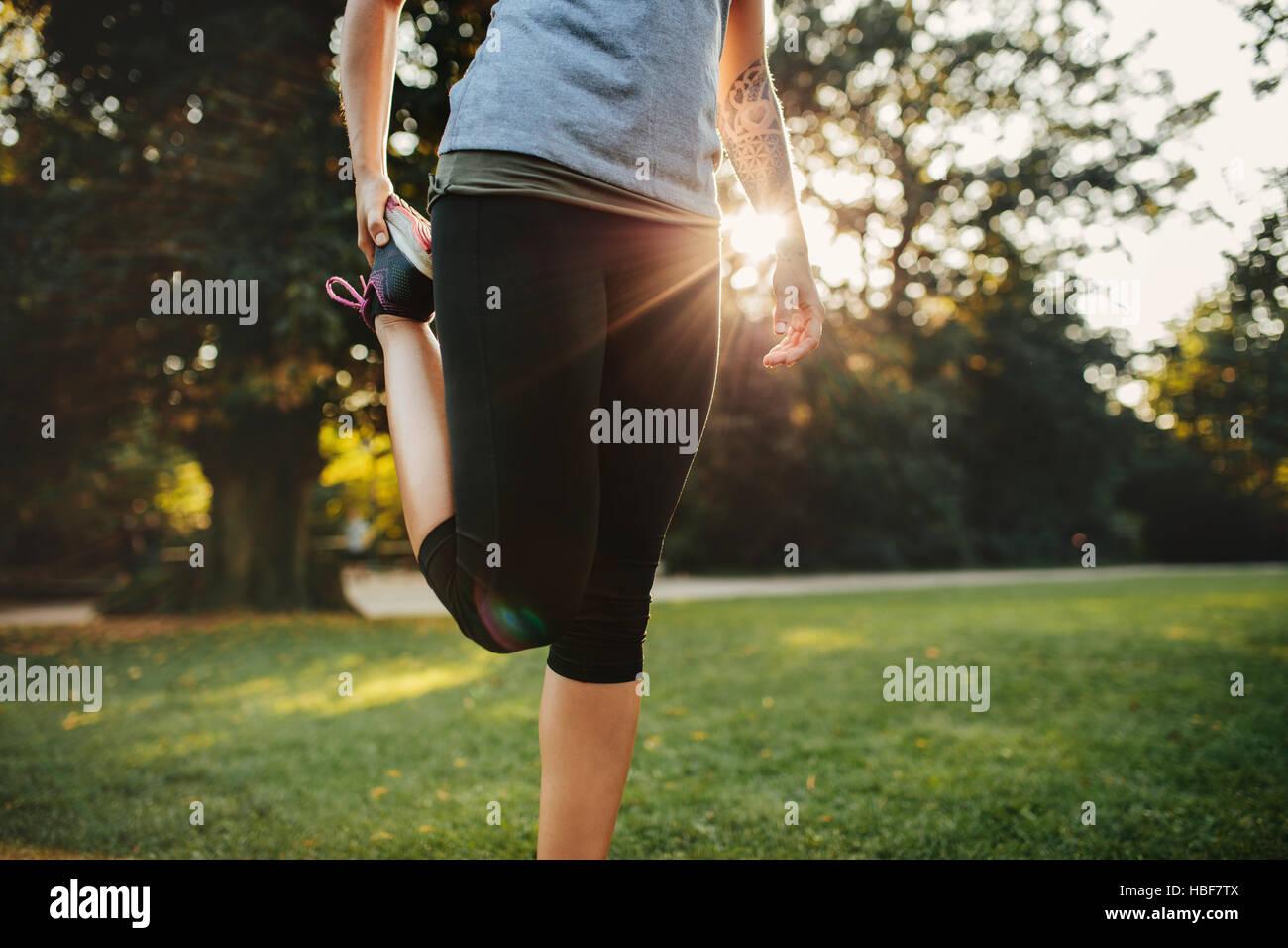 Schuss von Fitness-Frau, die Beine abgeschnitten. Weibliches Model Ausübung am Morgen am Stadtpark. Stockbild