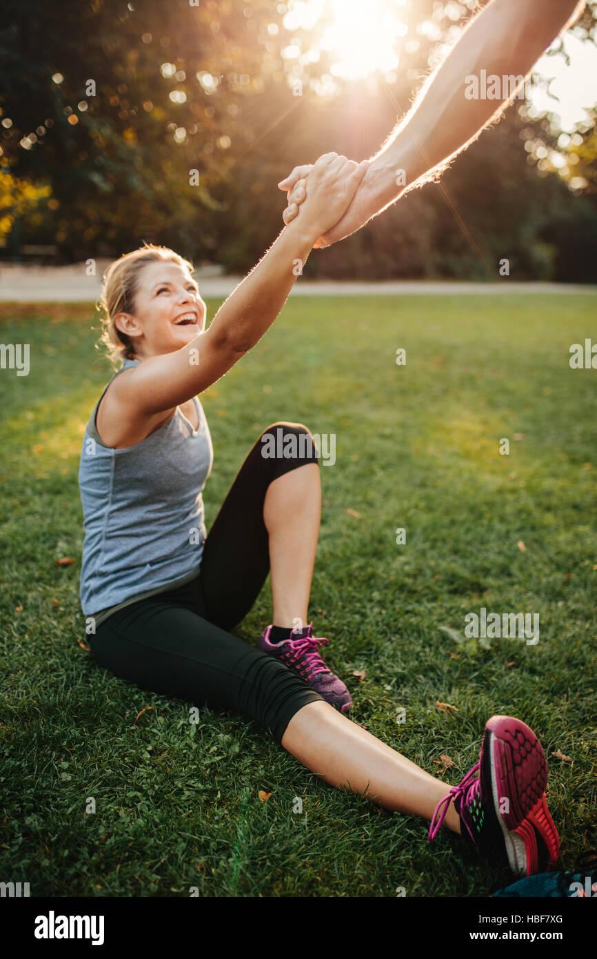 Schuss der Mann hilft Frau aufzustehen. Gesunde junge Paar im Park trainieren zusammen. Stockbild
