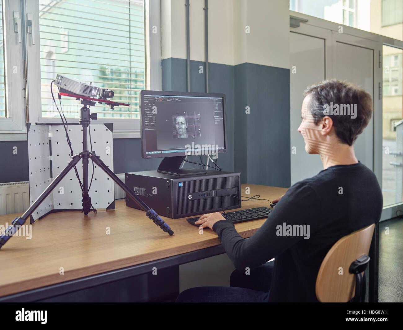 30-35 Jahre alte Frau scannt ihren Kopf mit einem 3D-Scanner Stockbild