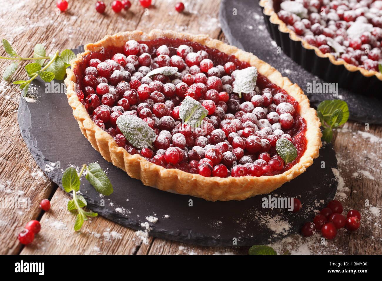Cranberry-Tarte mit Marmelade, Puderzucker und Minze-close-up auf dem Tisch. Horizontale Stockbild