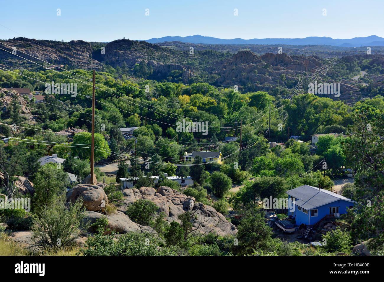 Robuste felsiges Gelände mit Häusern und Stromleitungen bis ins ferne, Granit Dells, Prescott, Arizona Stockbild