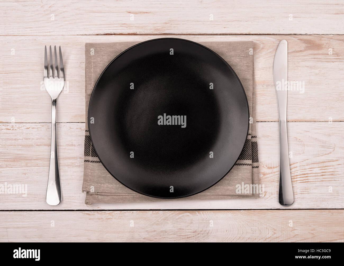 Draufsicht der leeren schwarzen Teller, Besteck und Serviette auf Holztisch Hintergrund Stockbild