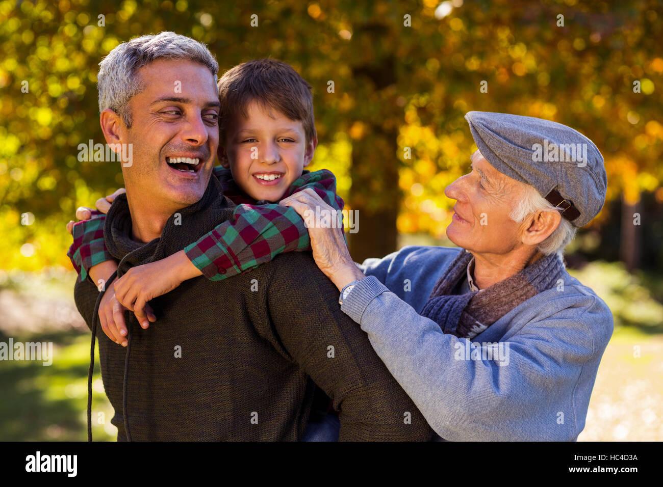 Glücklicher Mann Huckepack Sohn während mit Vater im park Stockbild