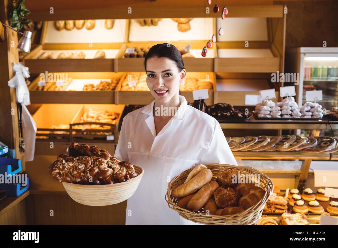 Weibliche Bäcker hält Korb mit süßen Speisen Stockbild