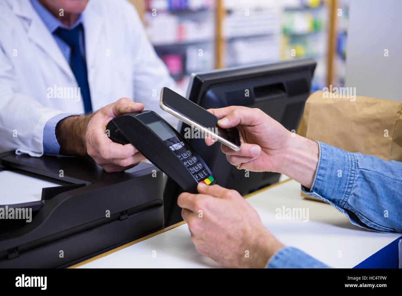 Kunde die Zahlung durch Smartphone in Zahlung terminal Stockfoto