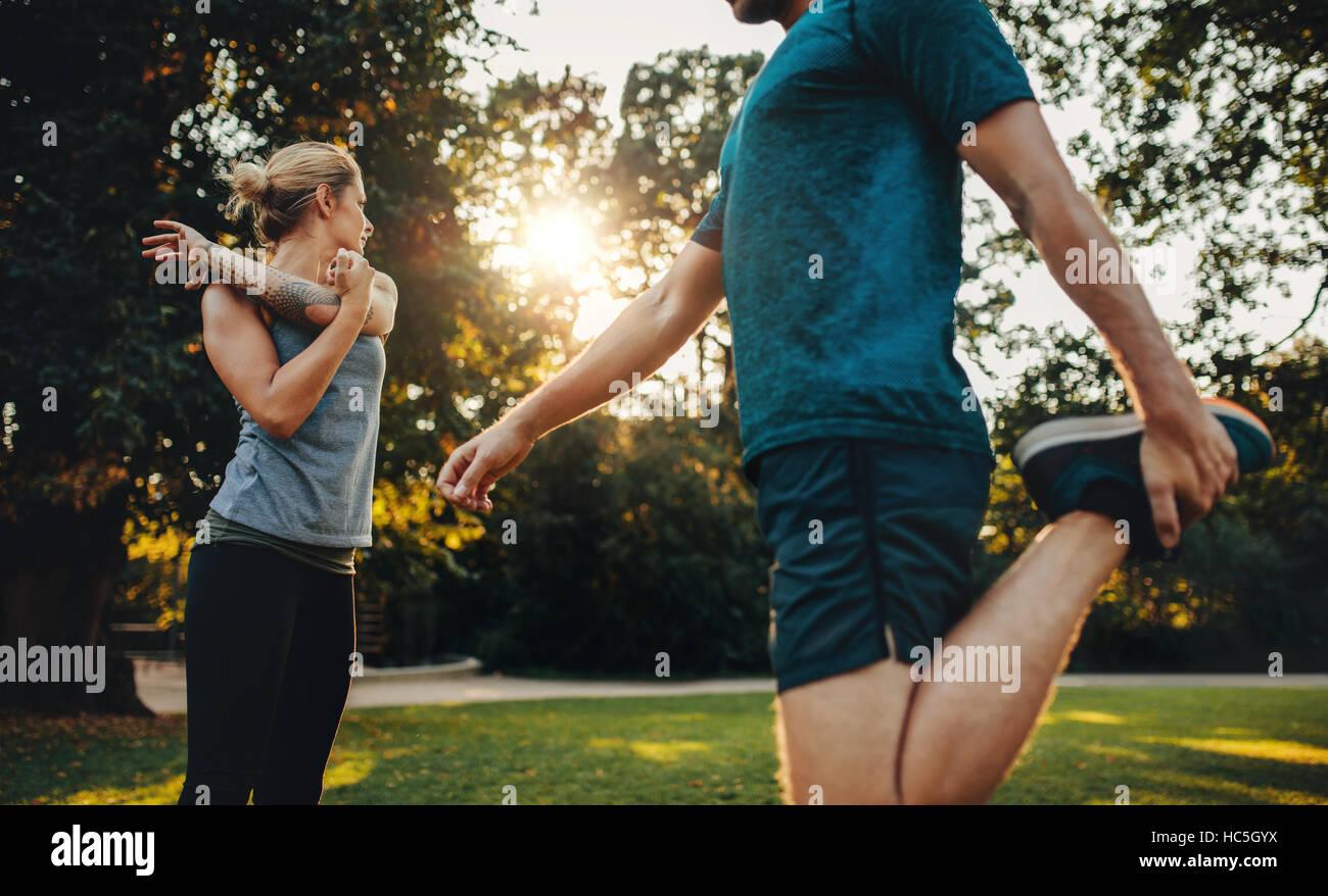 Aufnahme des jungen Mann und Frau, die stretching-Übung im Park zu tun. Junges Paar Aufwärmen für Stockbild