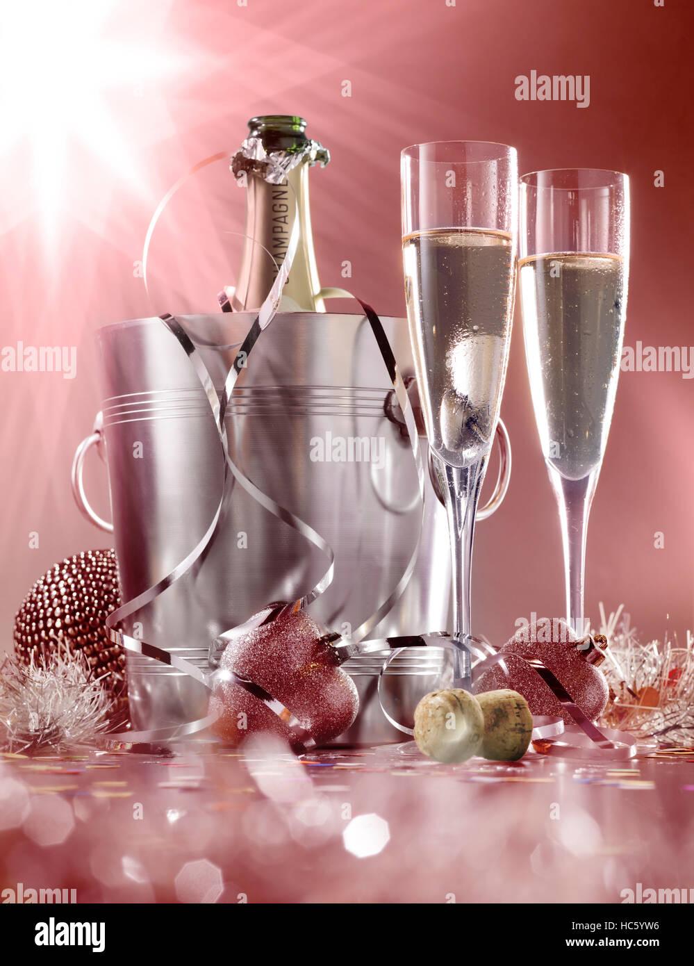 Glas Sekt mit Flasche im Kühler auf einem roten mit weißem Hintergrund Stockbild