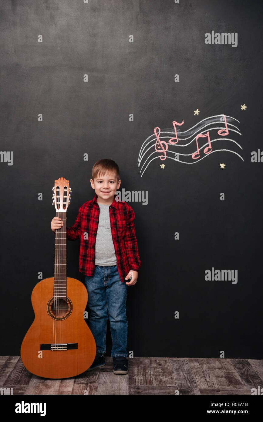 Foto von niedlichen kleinen Jungen halten die Gitarre im stehen in der Nähe von schwarzen Tafel mit musikalisch Stockbild