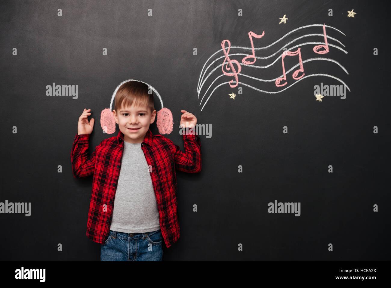 Bild von Geißlein Musikhören über schwarze Tafel mit musikalisch Zeichnungen Stockbild