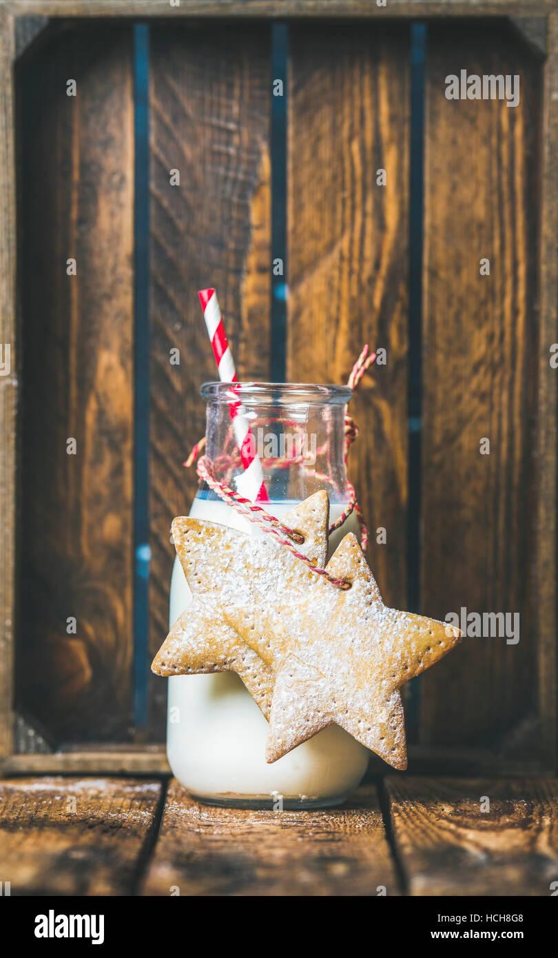 Flasche mit Milch und festliche Lebkuchen Sterne geformte Weihnachtsplätzchen mit Dekoration Seil auf hölzernen Stockbild
